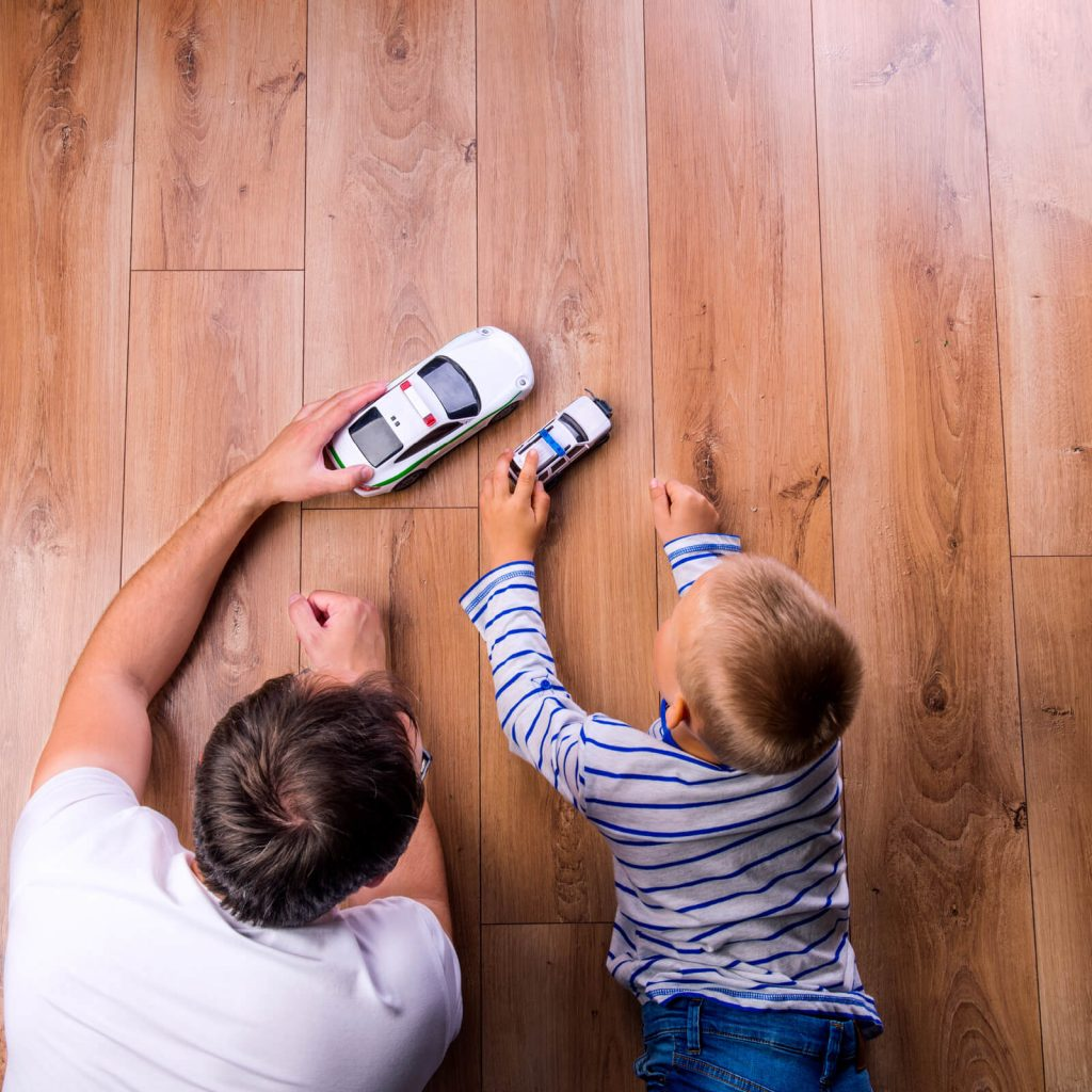 Father with kid playing with toycar | McCurleys National Flooring
